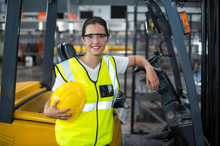 Portrait of smiling female worker standing in factory