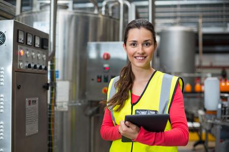 음료 생산 공장에서 디지털 태블릿을 들고 여성 공장 노동자의 초상화