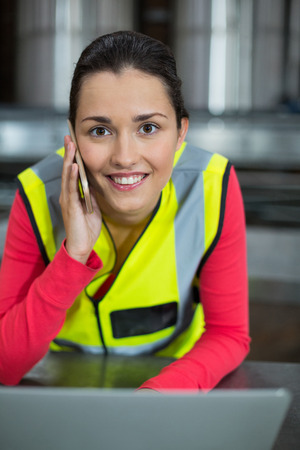 Portrait of female factory worker using laptop while talking on mobile phone at drinks production factory Stock Photo