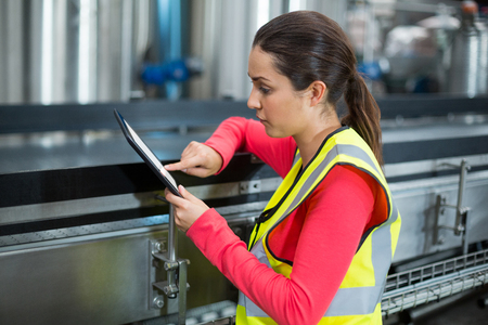 Female factory worker using digital tablet at drinks production factory Imagens - 72559730