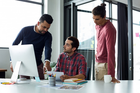 life partners: Businesspeople discussing over document in office