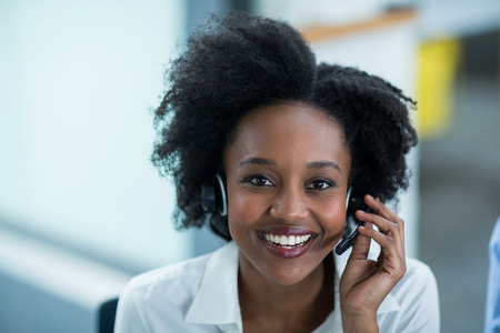Portrait of smiling business executives talking on headset in office Stock Photo