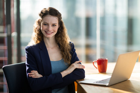 Portrait of smiling female business executive sitting in office with laptop on table