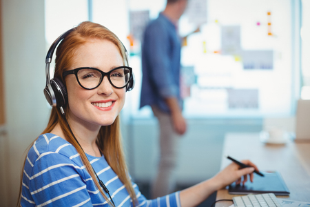 stylus: Female graphic designer working with headphones in office Stock Photo
