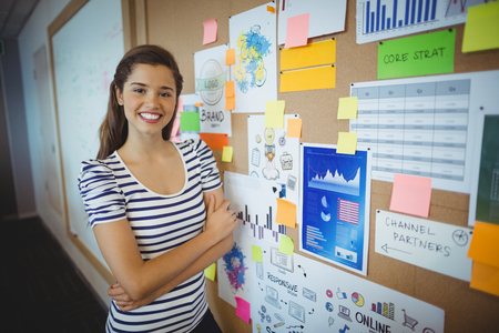 Portrait of female executive standing with arms crossed near bulletin board in office Stock Photo