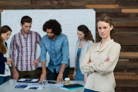 Portrait, femme affaires, debout, à, bras croisés, pendant, collègue, travailler, dans, fond, à, bureau