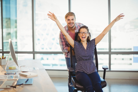 Playful man pushing his colleague on office chair in office