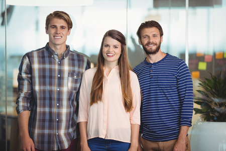 Portrait of happy business executives standing in office Stock Photo