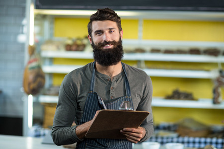 Portrait of salesman writing in clipboard at counter in grocery shop