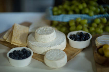 Variety of cheese and blue berry on counter at grocery shop