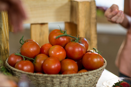 Basket of fresh tomatoes on the counter at grocery store Stock Photo