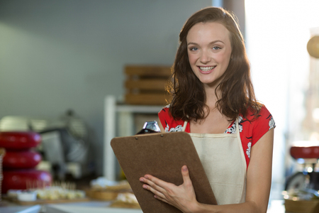 Female shop assistant writing on the clipboard at the counter in grocery shop Stock Photo