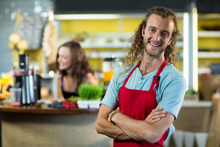 Smiling shop assistant standing in health grocery shop with his hands crossed