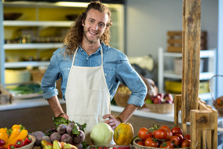 Vendor standing at the counter with hands on hips in the grocery store