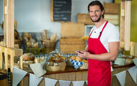 Portrait of smiling bakery staff using mobile phone at counter in bake shop Stock Photo