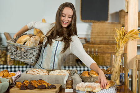 Smiling female staff putting bread in basket at counter in bake shop