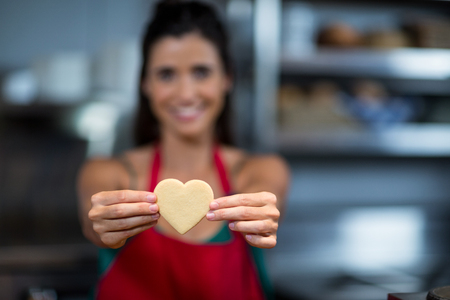 retailer: Close-up of female staff showing heart shape cookie at counter in bake shop