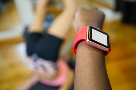 Close-up of womans hand using smart watch while workout in fitness studio