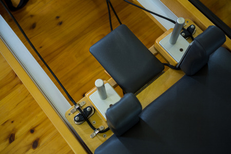 Close-up of reformer on wooden floor in gym