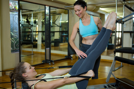 Female trainer assisting woman with stretching exercise in gym Stock Photo