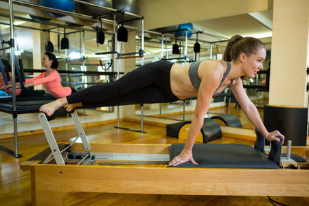 Determined woman practicing stretching exercise in gym Stock Photo