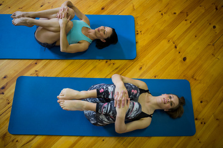 Fit women performing stretching exercise in gym