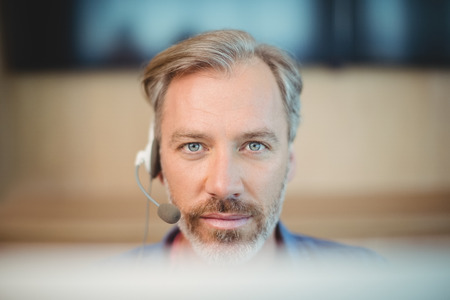 Male graphic designer working with headset in office Stock Photo