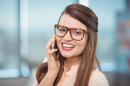 Portrait of female Executive talking on mobile phone in office Stock Photo