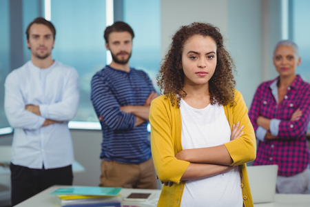 Portrait of executive standing with her colleagues in background in office Stock Photo