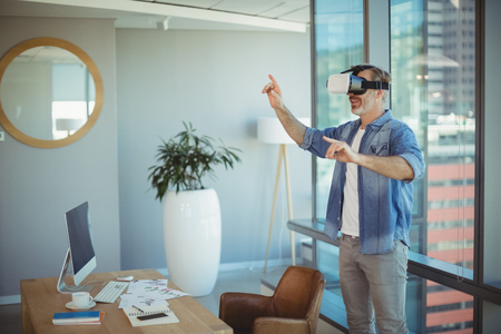 Male executive using virtual reality headset in office Stock Photo
