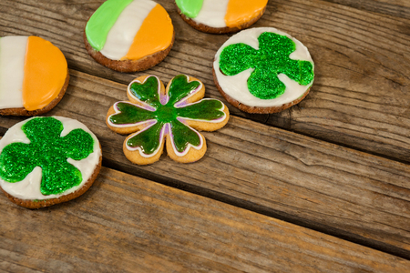 lucky charm: St. Patricks Day cookies decorated with irish flag and shamrock toppings on wooden background