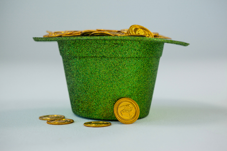 St. Patricks Day leprechaun hat filled with chocolate gold coins on white background Stock Photo