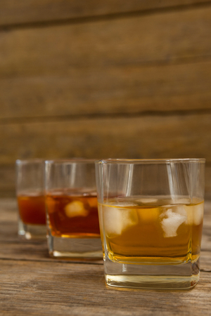 shinning: Three glasses of whiskey on wooden table Stock Photo