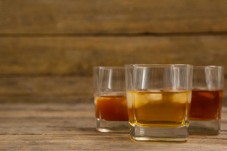Three glasses of whiskey with ice cube on wooden table