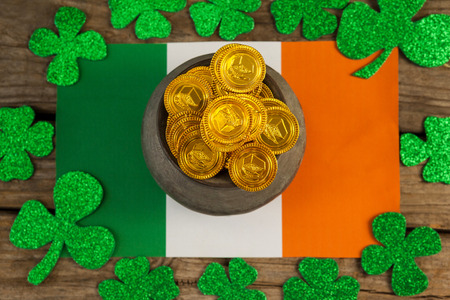 lucky charm: St. Patricks Day pot of chocolate gold coins and irish flag surrounded by shamrock on wooden table