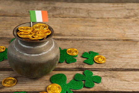 lucky charm: St. Patricks Day pot of chocolate gold coins with irish flag and shamrocks on wooden table