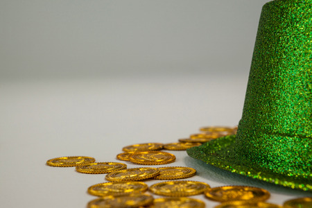 lucky charm: St Patricks Day leprechaun hat with gold chocolate coins on white background
