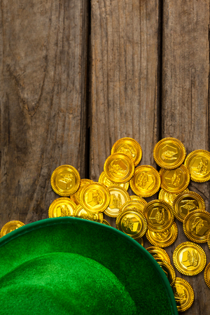 lucky charm: St Patricks Day leprechaun hat with gold chocolate coins on wooden background Stock Photo