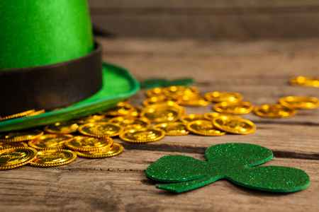 St Patricks Day leprechaun hat with shamrock and gold chocolate coin on wooden background Stock Photo