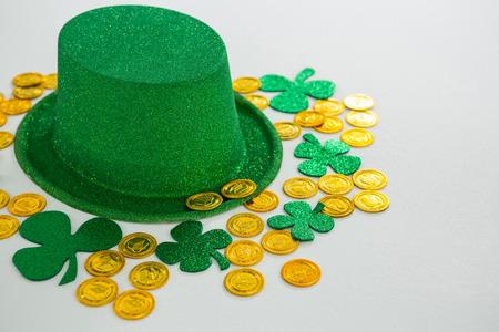 St. Patricks Day leprechaun hat, shamrocks and chocolate gold coins on white background