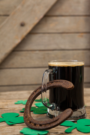 lucky charm: Glass of black beer, horseshoe and shamrock for St Patricks Day on wooden table