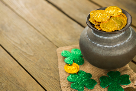 St. Patricks Day shamrock and pot filled with chocolate gold coins on wooden table