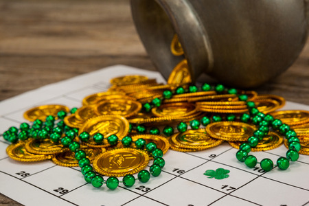 St. Patricks Day close-up of chocolate gold coins and beads kept on calendar Stock Photo