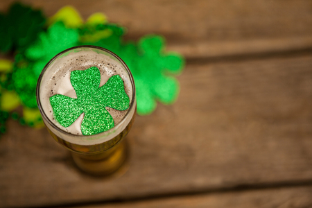 lucky charm: Glass of beer and shamrock for St Patricks Day against wooden background