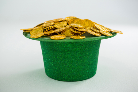 shinning: St. Patricks Day leprechaun hat filled with chocolate gold coins on white background Stock Photo