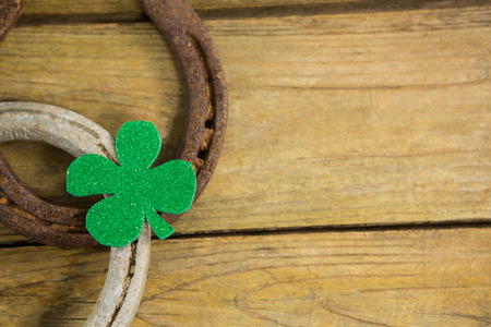 lucky charm: St Patricks Day shamrock with two horseshoes on wooden surface