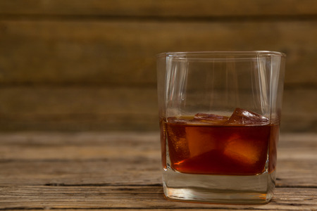 Glass of whisky with ice cube on wooden table Stock Photo