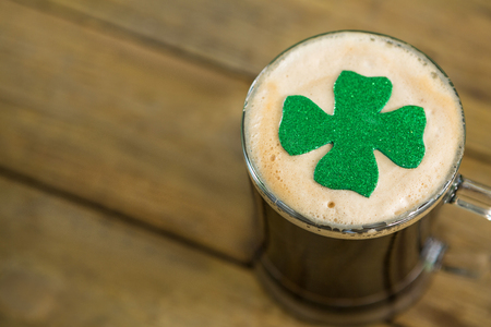 St Patricks Day mug of beer with shamrock on wooden surface
