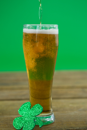 lucky charm: St Patricks Day beer with shamrock on wooden surface Stock Photo