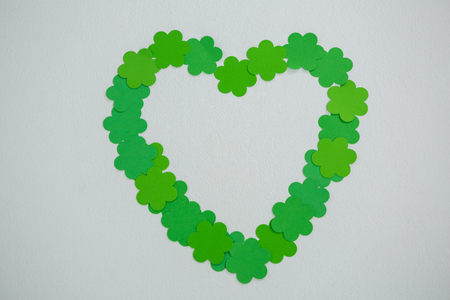 lucky charm: St Patricks Day shamrocks forming heart shape on white background Stock Photo